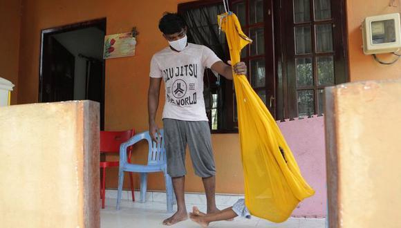 Prasad Dinesh, conductor de un bicitaxi al que las autoridades de Sri Lanka asocian con 1.100 contagios de coronavirus, incluidos 900 marinos, amaca a su hija en su casa de Ja-Ela el 1ro de julio del 2020. Dinesh era adicto a la heroína y dice que lo usan como chivo expiatorio. (AP Photo/Eranga Jayawardena).