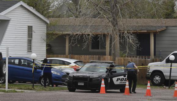 Un oficial de policía de Colorado Springs va a ayudar a una persona que estaba en una casa móvil diferente a poder llegar a su automóvil desde detrás de la cinta del crimen en Colorado Springs, Colorado. (Jerilee Bennett / The Colorado Springs Gazette vía AP)