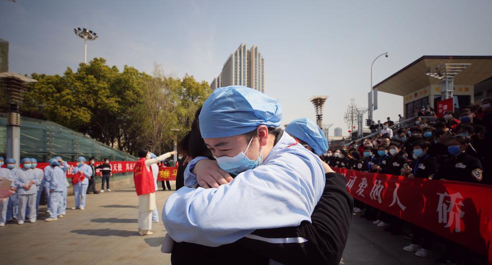 Trabajadores sanitarios que responden al COVID-19 se abrazan en Wuhan.  (Foto: STR / AFP) / China OUT
