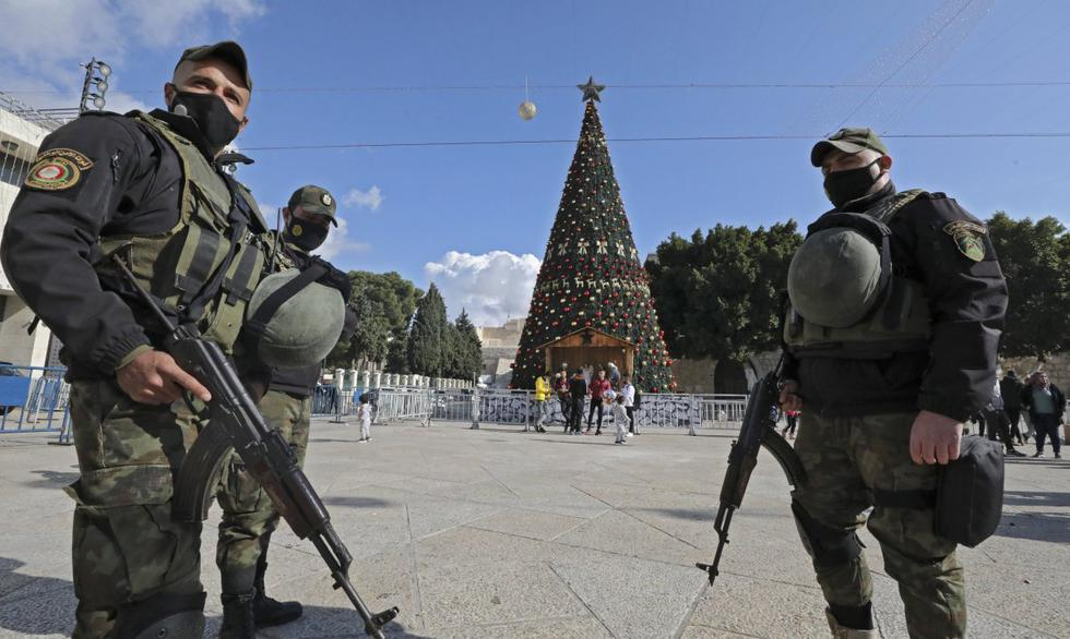 Miembros de las fuerzas de seguridad palestinas montan guardia frente a la Iglesia de la Natividad en la ciudad cisjordana de Belén.  Privado de su habitual afluencia turística por la pandemia, Belén celebrará una tranquila Navidad este año que se trata menos de comercio y más de religión, dice su párroco. (Foto: HAZEM BADER / AFP)