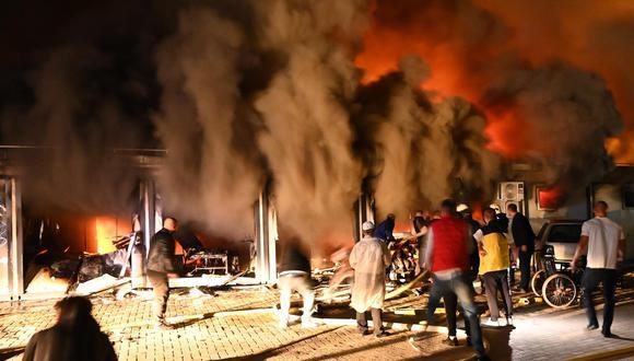 El humo se eleva mientras los bomberos y los civiles intentan extinguir un incendio que estalló en un hospital para pacientes de coronavirus covid-19 en Tetovo, República de Macedonia del Norte. (EFE / EPA / STRINGER).