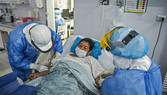 Los profesionales de la salud ayudan a un paciente con COVID-19 en la Unidad de Cuidados Intensivos del Hospital Alberto Sabogal Sologuren, en Lima, en medio de la nueva pandemia de coronavirus. (Foto: Ernesto BENAVIDES / AFP)