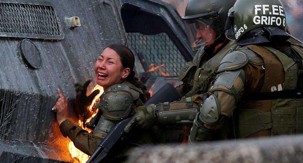 Una carabinera es alcanzada por una bomba molotov durante una protesta en Santiago de Chile. REUTERS/Jorge Silva).