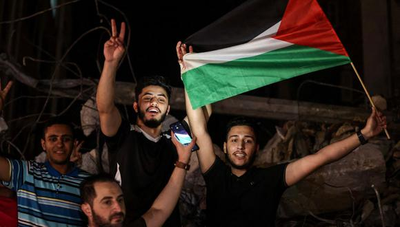 La gente agita la bandera palestina mientras celebra en la calle tras un alto el fuego negociado por Egipto entre Israel y los dos principales grupos armados palestinos en la ciudad de Gaza. (MOHAMMED ABED / AFP).