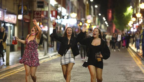 Jóvenes disfrutan de la noche en el centro de Liverpool el 10 de octubre de 2020 antes de que entren en vigor restricciones en los horarios de los bares debido al aumento de casos de coronavirus. (Peter Byrne/PA vía AP).