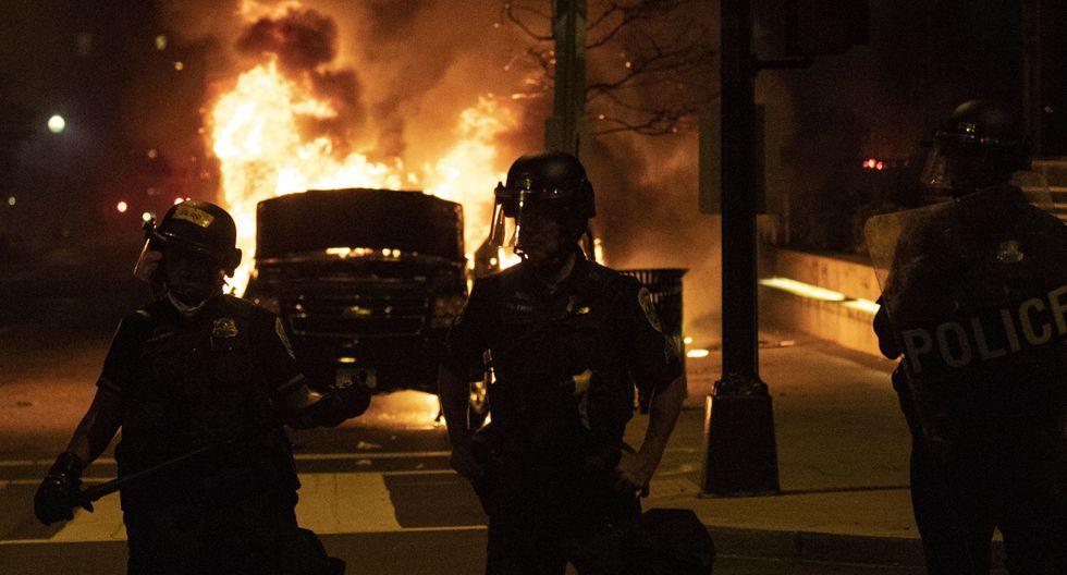 Policías bloquean una calle junto a un auto en llamas a una cuadra de la Casa Blanca el 30 de mayo de 2020 en Washington DC, durante una protesta por la muerte de George Floyd. (Foto por Eric BARADAT / AFP).