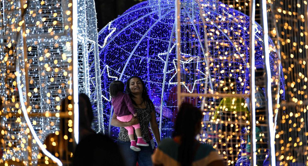 La gente visita la decoración navideña colocada a lo largo de la avenida Los Próceres en Caracas. (AFP / Yuri CORTEZ).