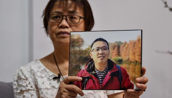 Zhong Hanneng muestra un retrato de su hijo Peng Yi, quien murió por el coronavirus COVID-19 en la ciudad de Wuhan. (Foto de Hector RETAMAL / AFP).