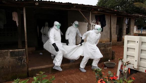 Personal médico de Liberia transporta el cuerpo de una víctima del ébola desde una casa para enterrarlo en la comunidad de Banjor, en las afueras de Monrovia, el 6 de agosto de 2014. (EFE / EPA / AHMED JALLANZO).