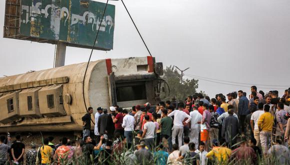 La gente observa cómo una grúa levanta un vagón de un tren de pasajeros volcado en la ciudad de Toukh, Egipto. (Foto de Ayman AREF / AFP).