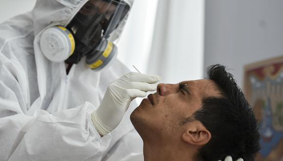 Un trabajador de salud toma una muestra a una persona en Colombia. (Foto: Luis ROBAYO / AFP)