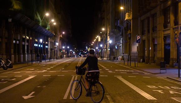 Una mujer anda en bicicleta por una calle desierta en medio de un toque de queda establecido para luchar contra la propagación del coronavirus, en Barcelona, el 26 de octubre de 2020. (Josep LAGO / AFP).