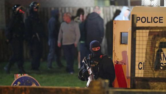 Policía armada se encuentra en la escena de disturbios en Creggan, Londonderry, en Irlanda del Norte. (Foto: AP)