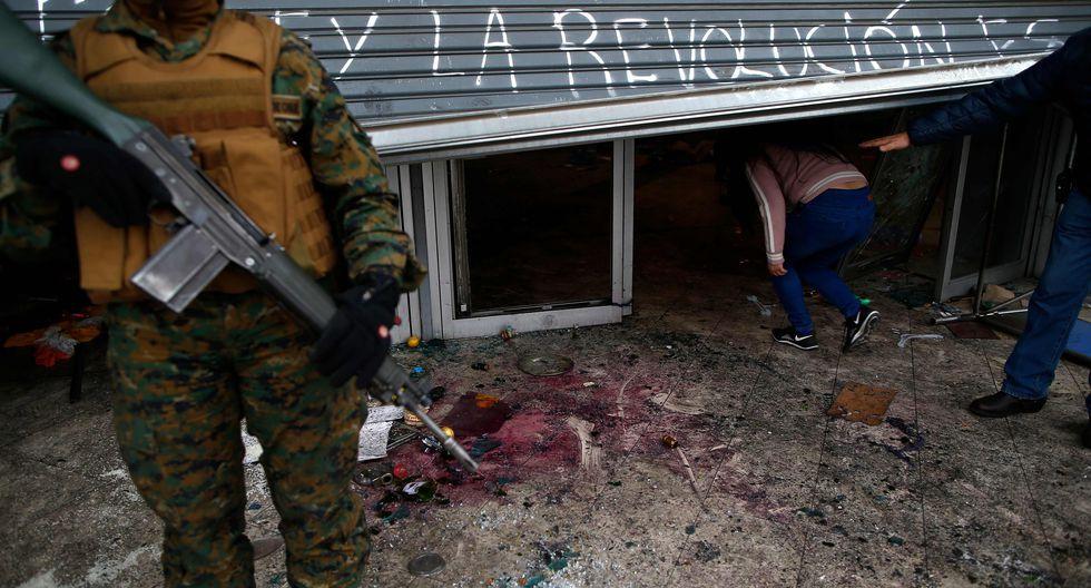 Militares resguardan un negocio saqueado en Santiago de Chile. (AFP / Pablo VERA).