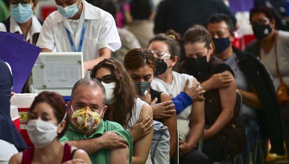 La gente espera luego de recibir dosis de la vacuna Pfizer-BioNTech contra COVID-19 en un centro de vacunación para mayores de 50 años instalado en la Biblioteca Vasconcelos, en la Ciudad de México. (Foto: Pedro Pardo / AFP)