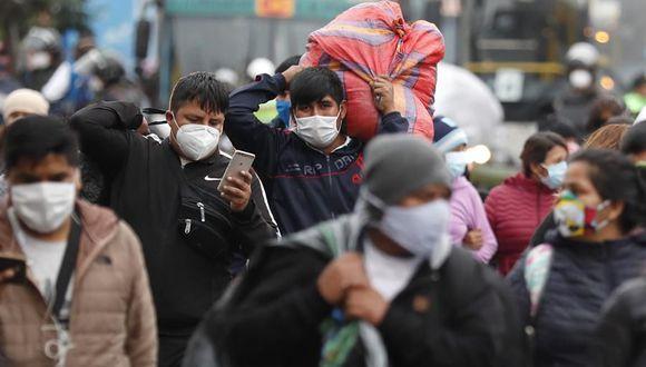 Vendedores ambulantes se desplazan luego de ser desalojados por la policía de una vía pública donde trabajaban en Lima, Perú, país seriamente golpeado por la pandemia de coronavirus. (EFE/Paolo Aguilar).