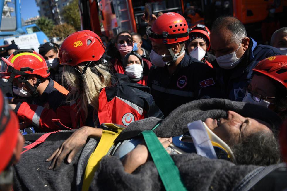Los equipos de búsqueda y rescate llevan a Sefer Perincek, madre de tres hijos, luego de sacarla de entre los escombros de un edificio derrumbado en Esmirna, Turquía. (Foto de OZAN KOSE / AFP).