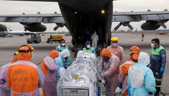 Personal sanitario de la Fuerza Aérea de Chile (FACH) e integrantes del Servicio de Atención Médica de Urgencia SAMU (de naranja) llevan a un avión a un paciente crítico de coronavirus COVID-19. (EFE/Alberto Valdés).
