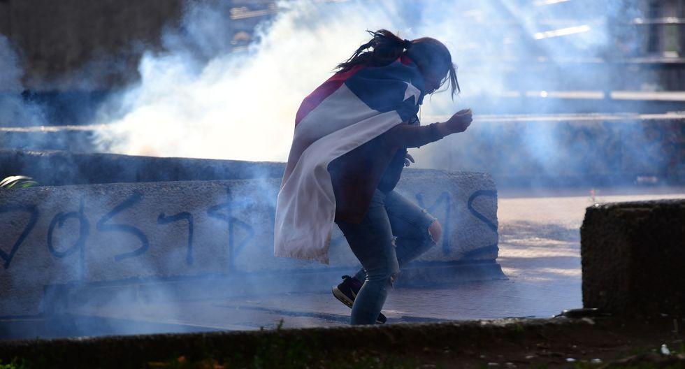 Una manifestante corre para escapar de los gases lacrimógenos en Santiago. (Photo by Martin BERNETTI / AFP).