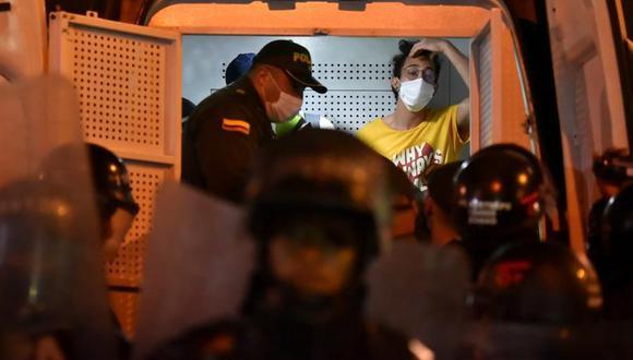 Un hombre permanece detenido al interior de un vehículo de la policía durante una manifestación contra el abuso policial en Cali. (EFE/ Ernesto Guzmán Jr).