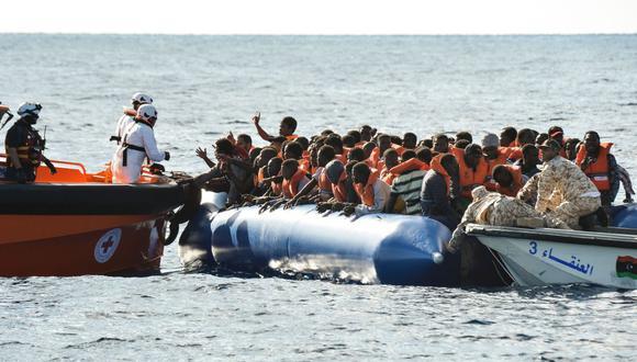 Migrantes y refugiados se sientan en un bote de goma durante una operación de rescate. (Foto referencial, AFP / ANDREAS SOLARO).