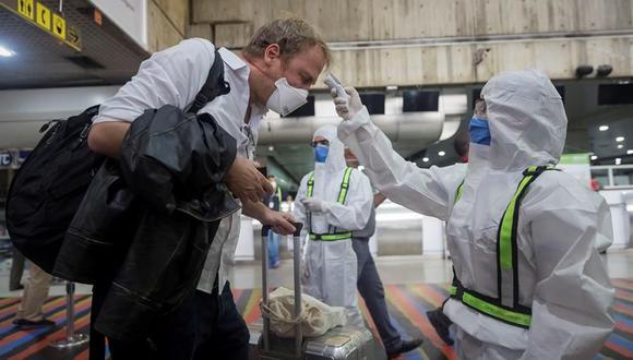 Un trabajador sanitario toma la temperatura a un pasajero en el Aeropuerto Internacional Simón Bolívar de Maiquetía, en La Guaira, Caracas, Venezuela. (EFE/Rayner Peña R./Archivo).