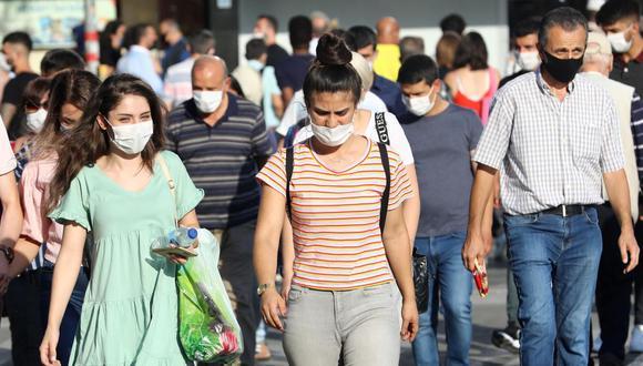 Imagen referencial. Las personas usan sus máscaras protectoras por el coronavirus mientras caminan por una calle en Ankara (Turquía. (AFP / Adem ALTAN).