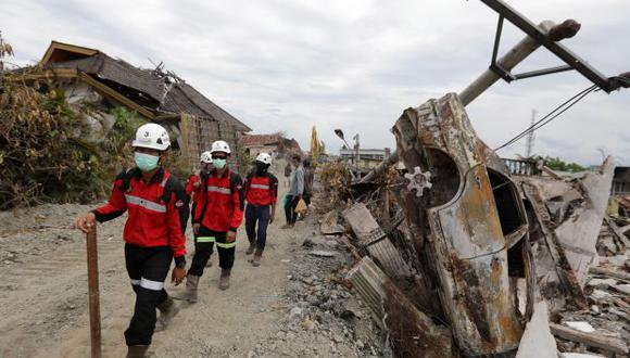 """Un hombre fotografía el estado de una vivienda dañada en el terremoto y posterior tsunami en Palu, en la isla indonesia de Célebes, junto a la frase """"por favor, ayuda"""". (Foto: EFE)"""
