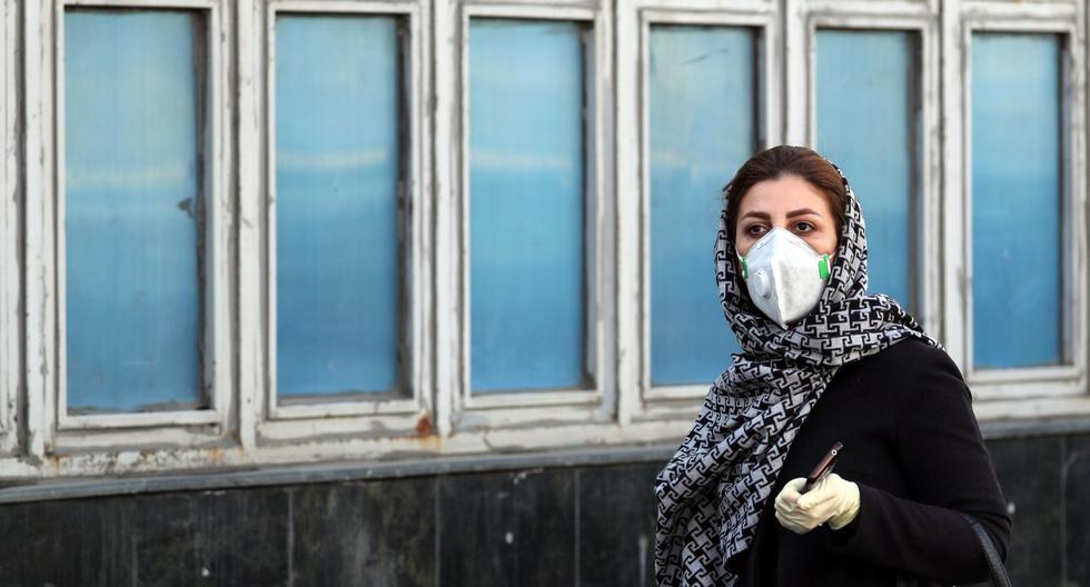 Una mujer iraní que lleva mascarilla y guantes protectores contra el coronavirus camina en Teherán. (EFE / EPA / ABEDIN TAHERKENAREH).