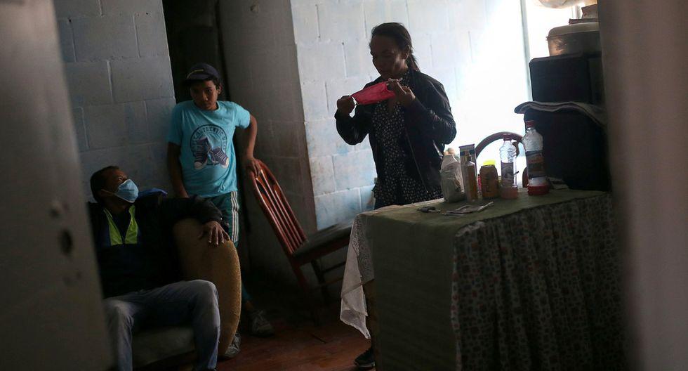 Una mujer se prepara para usar una máscara facial dentro de su hogar, en medio del brote de la enfermedad por coronavirus (COVID-19) en Soacha, Colombia. (Foto: Reuters/Luisa Gonzalez)