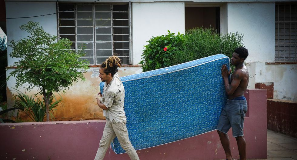 Cubans take a mattress to a safe place in Havana, on September 9, 2017. - Irma's blast through the Cuban coastline weakened the storm to a Category Three, but it is still packing 125 mile-an-hour winds (205 kilometer per hour) and was expected to regain power before hitting the Florida Keys early Sunday, US forecasters said. The Cuban government extended its maximum state of alert to three additional provinces, including Havana, amid fears of flooding in low-lying areas. (Photo by YAMIL LAGE / AFP)