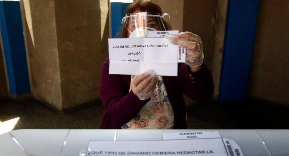 Una empleada del Servicio Electoral de Chile (Servel) muestra a la prensa la boleta que será usada en el referéndum para cambiar la constitución de la era de la dictadura militar del país, en un centro de votación en Santiago. (Foto: AFP / ATON CHILE / Javier Salvo)