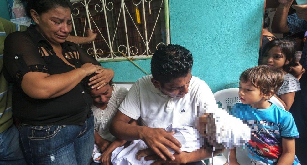 Claudia Bermúdez (i) consuela a su hermana, Karina Navarrete Sánchez (i2), mientras Nelson Gabriel Lorio (c), carga el cuerpo de su hijo, Teyler Leonardo, de 14 meses, durante su velatorio. (Foto: EFE/Douglas López)