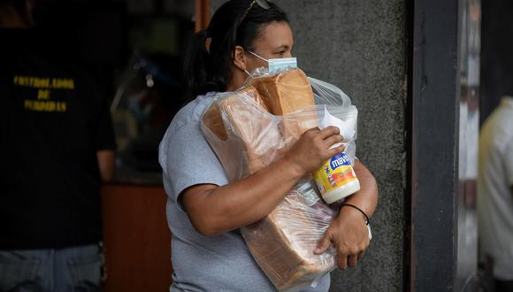 Una mujer carga sus compras mientras sale de un supermercado, el 14 de abril de 2021, en Caracas, Venezuela. (Foto: EFE/RAYNER PEÑA R.).