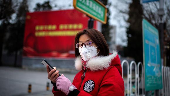 Una mujer con una máscara protectora para protegerse contra el coronavirus COVID-19 mira su teléfono mientras en una calle en Beijing, China. (Foto por NICOLAS ASFOURI / AFP).