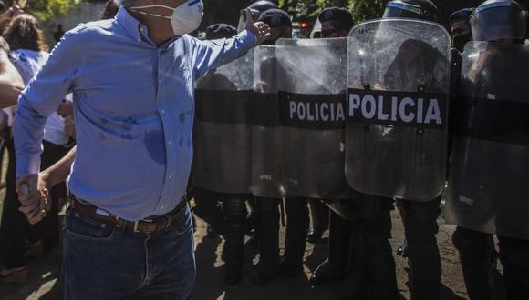 El periodista nicaragüense Carlos Fernando Chamorro, director de Confidencial, es empujado por la policía antidisturbios frente a las oficinas de su diario el 14 de diciembre de 2020. (Foto de STR / AFP).