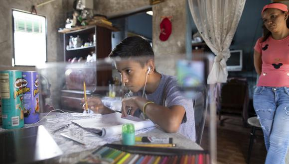 Samuel Andrés Mendoza mira una imagen de un Pokemon en su computadora antes de dibujarla en su casa en Barquisimeto, Venezuela, el martes 2 de marzo de 2021. El joven de 14 años ha estado vendiendo sus dibujos en su cuenta de Twitter para ayudar a su familia. (AP Foto/Ariana Cubillos).