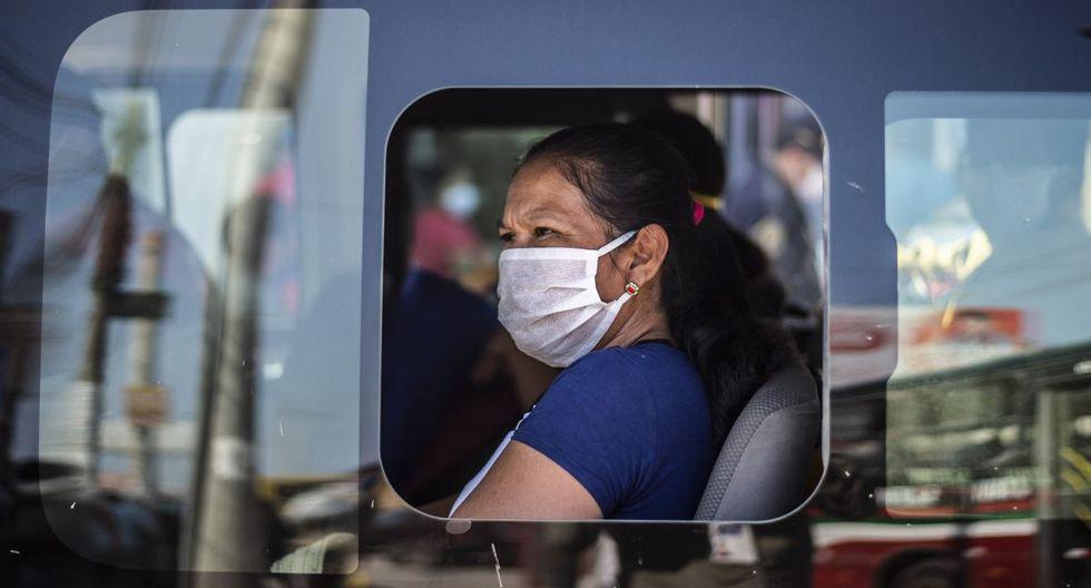 Una mujer con una mascarilla en una unidad de transporte público fuera del mercado de Ciudad de Dios, en Lima (Foto: ERNESTO BENAVIDES / AFP)