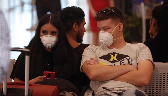 Pasajeros y empleados del Aeropuerto de Ezeiza usan mascarillas, tras la confirmación del primer caso del Coronavirus en el país, este miércoles, en Buenos Aires. (Foto: EFE)