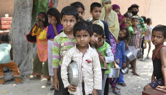 Niños de un barrio marginal hacen cola para obtener comida gratis después de que el gobierno de la India alivió el confinamiento decretado para frenar el coronavirus COVID-19. (Foto: Prakash SINGH / AFP).