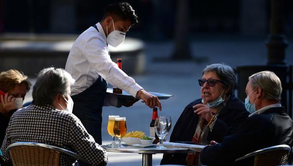 Un camarero atiende a los clientes en un restaurante de Barcelona el 23 de noviembre de 2020 tras la reapertura de bares, restaurantes y cines después de estar cerrados durante más de un mes para frenar el coronavirus. (Foto de LLUIS GENE / AFP).
