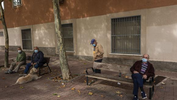 Ancianos con mascarillas para prevenir la propagación del coronavirus se sientan en un parque en el barrio sureño de Vallecas, en Madrid, España. (Archivo/AP/Bernat Armangue)
