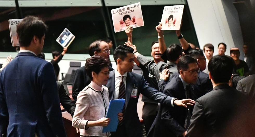 Carrie Lam deja Parlamento por segunda vez tras intentar dar su discurso anual sobre las políticas del gobierno. Legisladores prodemocráticos (en el fondo) la interceptan en el Consejo Legislativo en Hong Kong. (AFP)