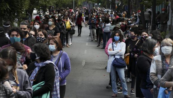 La gente hace fila y espera su turno para votar durante un plebiscito que decidirá si el país sudamericano reemplaza su constitución de 40 años, en Santiago de Chile, el domingo 25 de octubre de 2020 (AP Foto/Esteban Félix).