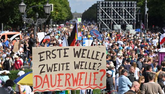 """Los participantes sostienen un cartel que dice """"¿Primera ola, segunda ola, ola permanente?"""" durante una protesta en Berlín convocada por la extrema derecha y los negacionistas del coronavirus. (Foto) John MACDOUGALL / AFP)."""
