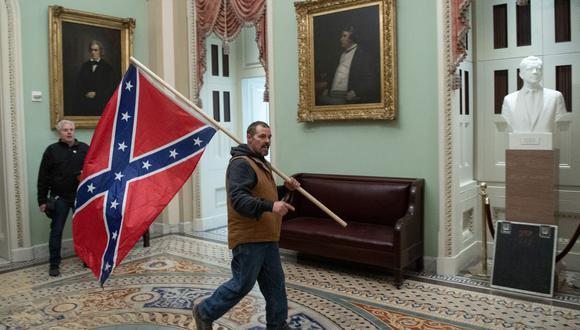 Un partidario del presidente de Estados Unidos, Donald Trump, lleva una bandera confederada mientras protesta en la Rotonda del Capitolio el 6 de enero de 2021. (Foto de SAUL LOEB / AFP).