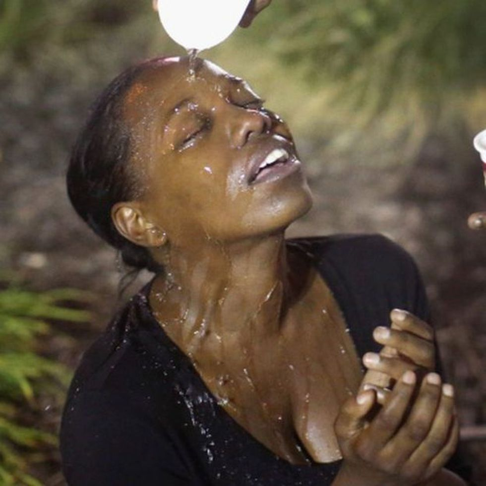 Una mujer en la localidad de Ferguson, Misuri, se limpia el rostro con agua después de un ataque con gas lacrimógeno.
