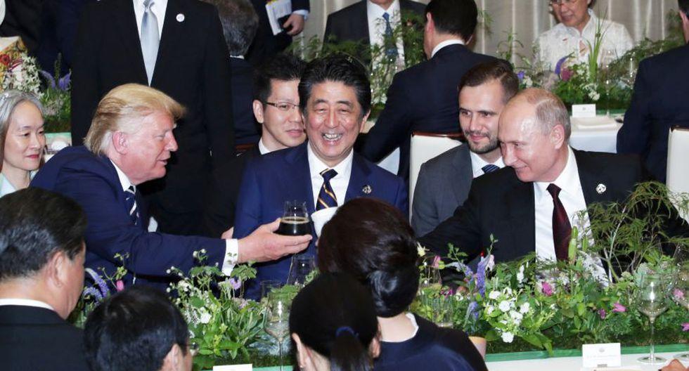 En la imagen se puede observar al presidente estadounidense Donald Trump y al mandatario ruso Vladimir Putin brindando. El primero con una copa de vidrio y el segundo con un termo. (Reuters)