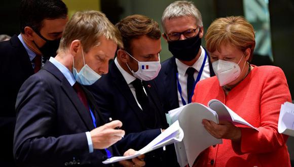 El presidente de gobierno de España, Pedro Sánchez (izquierda); el presidente francés Emmanuel Macron (centro) y la canciller alemana Angela Merkel (derecha) examinan documentos durante una cumbre de la Unión Europea en Bruselas. (Foto: JOHN THYS / POOL / AFP).