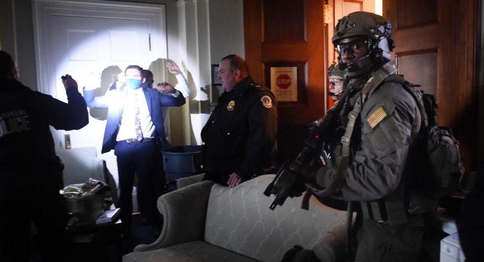 El personal del Congreso levanta las manos mientras los equipos Swat de la Policía del Capitolio revisan a todos en la sala mientras aseguran el piso de los partidarios de Trump en Washington. (Foto: AFP / Olivier DOULIERY).